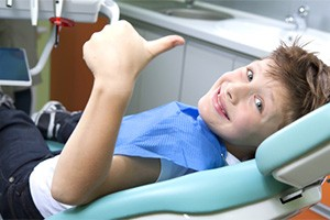 child in dental chair giving thumbs up