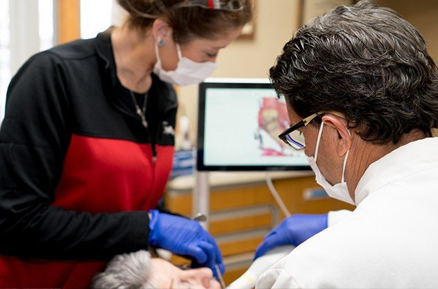 Patient receiving dental care from dentist and team member